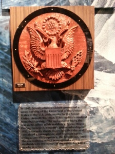 "Pictured: A mold of a ""gift"" crafted by Soviet children during the Cold War. The plaque reads, ""In 1945, Soviet school children presented a wood carving of the Great Seal of the United States to the U.S. ambassador to the Soviet Union, Averell Harriman. (This replica is molded from that carving.) The ambassador hung the seal in his office of his residency, Spaso House. During George F. Kennan's ambassadorship in 1952, a security check discovered that the seal contained a microphone and resonant cavity. Using a specific frequency. the Soviets activated the microphone which transmitted a signal, modulated by the voices in the room, back to a nearby receiver."""